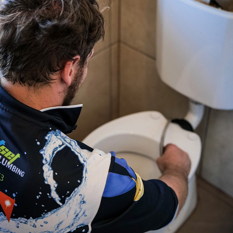 Plumber fixing a toilet